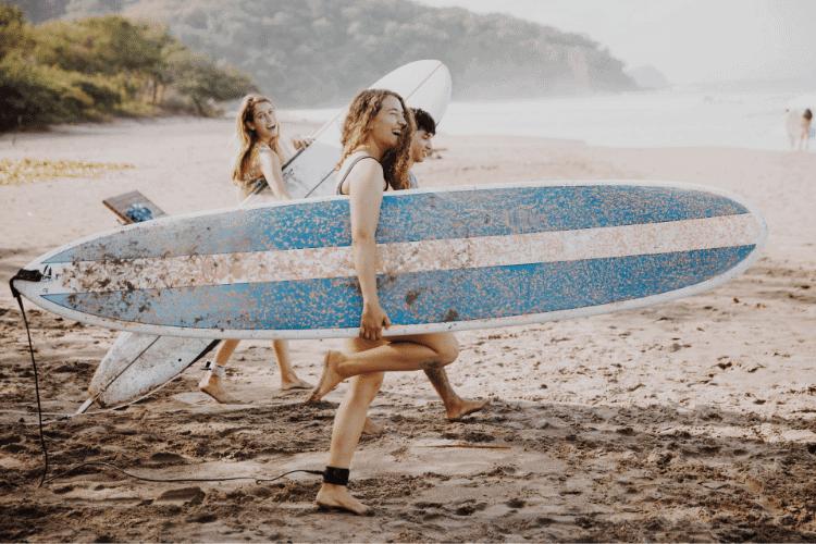 Group of Surfers headed walking across beach to ocean