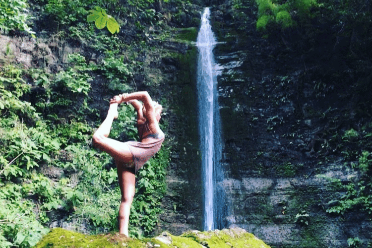 Woman in Dancers Yoga Pose in front of waterfall
