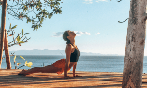 woman doing yoga, updog, on studio deck with ocean in background