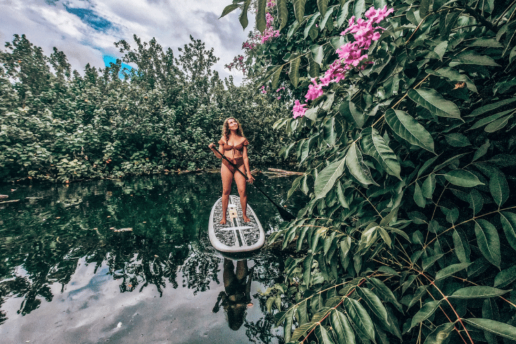 Woman paddleboarding down river with lush plants and flowers